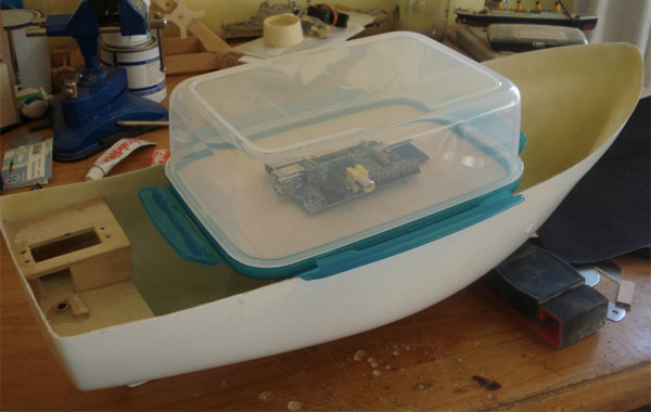 Raspberry Pi, protetto da una scatola in plastica del tipo per la conservazione di alimenti, è il pilota del piccolo battello FishPi (lungo circa 50 cm), utilizzando la guida di un GPS e una bussola.
